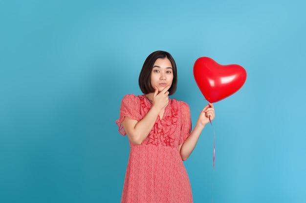 Taciturna jovem asiática de vestido vermelho segura um balão vermelho voador em forma de coração e esfrega o queixo