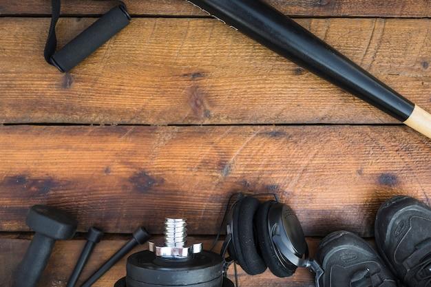 Taco de beisebol; alça de fitness; halteres; pular corda; pesos; fone de ouvido e sapatos no plano de fundo texturizado de madeira