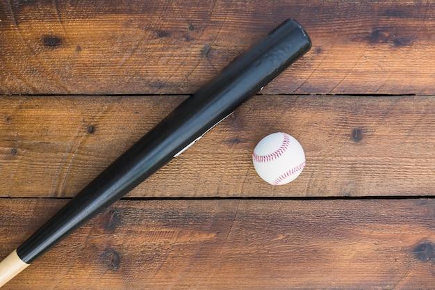 Taco de beisebol e beisebol na mesa de madeira