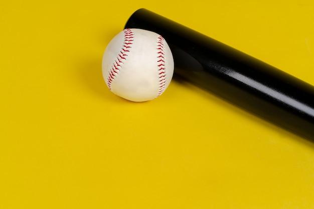 Taco de beisebol e bola em fundo amarelo brilhante