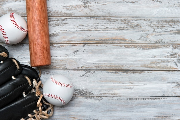Taco de beisebol, luva e bola em fundo de madeira