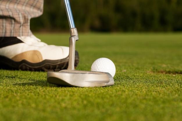 Taco de golfe batendo bola de golfe