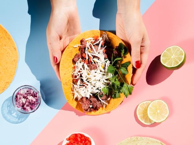 Taco de vista superior com carne e legumes na mão