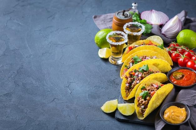 Taco shell e milho tortilla chips nachos com carne moída, picadinho, guacamole, molho de pimenta jalapeño e molho de queijo com tequila ou cerveja em uma mesa. vista superior do plano de fundo do espaço da cópia