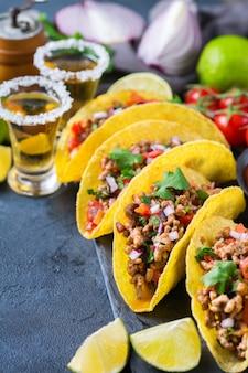Taco shell e milho tortilla chips nachos com carne moída, picadinho, guacamole, molho de pimenta jalapeño e molho de queijo com tequila ou cerveja em uma mesa.