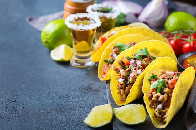 Taco shell e milho tortilla chips nachos com carne moída, picadinho, guacamole, molho de pimenta jalapeño vermelho quente e molho de queijo com tequila ou cerveja em uma mesa. copie o fundo do espaço
