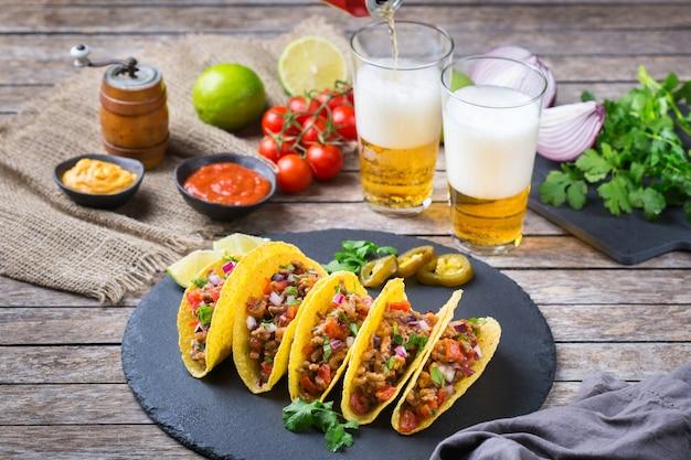 Taco shell e milho tortilla chips nachos com carne moída, picadinho, guacamole, molho de pimenta jalapeño vermelho quente e molho de queijo com tequila ou cerveja em uma mesa.