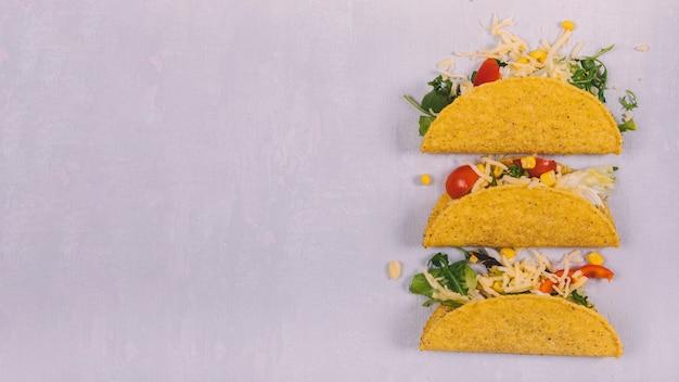 Tacos com carne e legumes dispostos em fundo de concreto