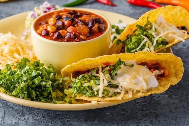 Tacos com chili com carne, salada, queijo e creme de leite
