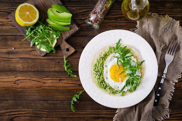 Tacos com guacamole, ovo frito e rúcula. comida saudável. café da manhã útil. lay plana. vista do topo
