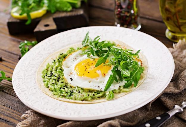Tacos com guacamole, ovo frito e rúcula. comida saudável. café da manhã útil.