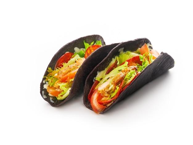 Tacos com legumes grelhados, cebola e pimentão em pão de tortilhas pretas, conceito de fast food mexicano