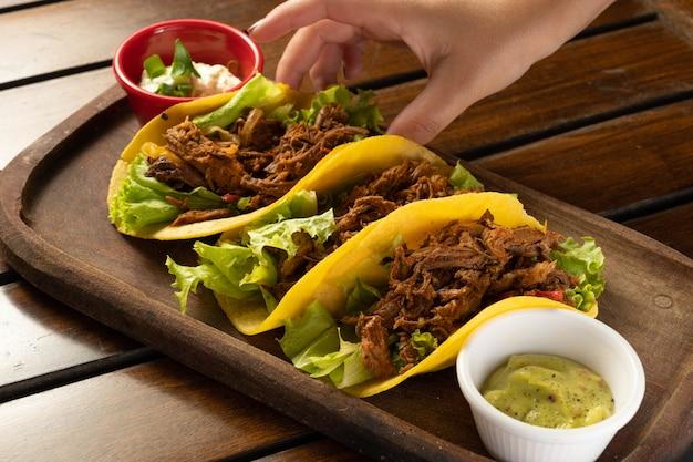 Tacos de carne. comida tradicional mexicana. mão pegando taco.