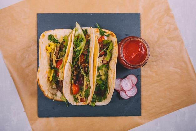 Tacos de carne mexicana com legumes e molho de tomate na ardósia preta