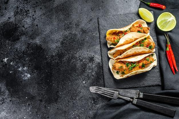 Tacos de carnitas mexicanos com salsa, queijo e pimenta malagueta. fundo preto