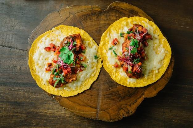 Tacos de frango grelhado com salada de tomate servido na tábua de madeira.