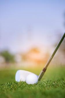 Tacos de golfe e bolas de golfe em um gramado verde em um belo campo de golfe ao amanhecer
