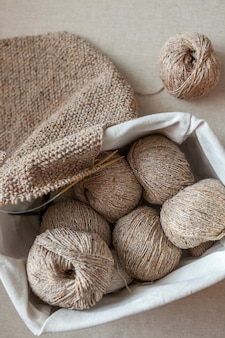 Tacos de lã e um lenço de crochê em uma cesta. vista superior, foco seletivo.