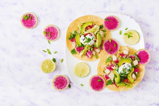 Tacos de milho mexicano saudáveis com peito de frango cozido, rabanete de abacate e melancia e molho de iogurte.