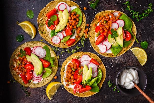 Tacos do vegetariano com grãos-de-bico cozidos, abacate, molho e vegetais, vista superior.