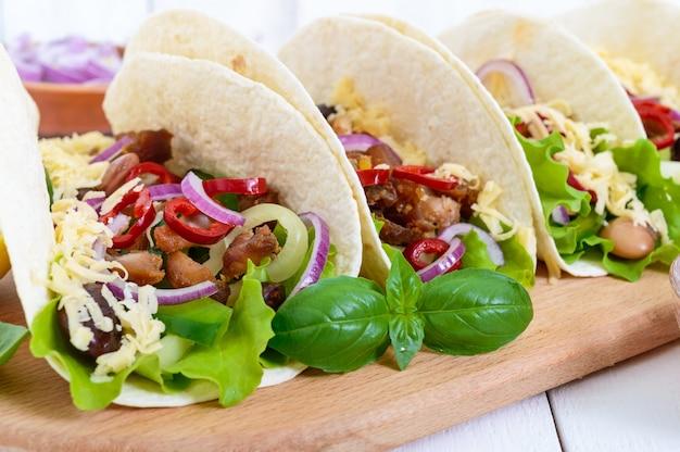 Tacos é um prato tradicional mexicano. tortilla recheada com frango, pimentão e pimenta, feijão, alface, queijo, cebola azul com molho de salsa em fundo branco de madeira.