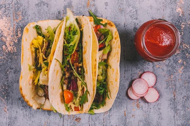 Tacos e vegetais mexicanos da carne na tortilha com molho de tomate no fundo resistido