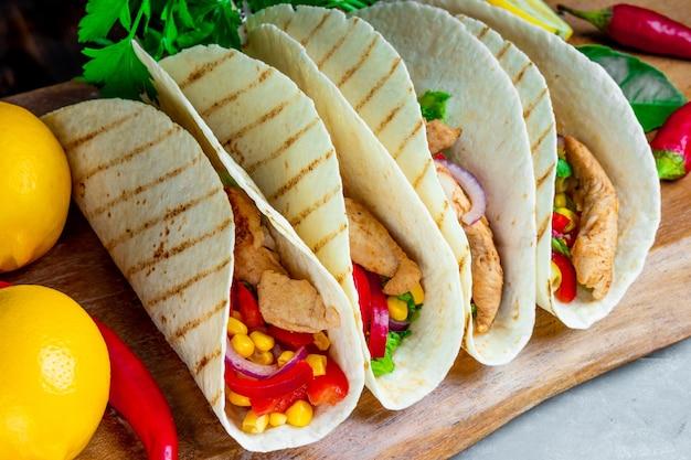 Tacos latino-americanos com frango e milho em uma tábua de madeira de perto