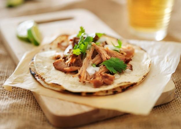 Tacos mexicanos autênticos com carnitas, coentro e cebola