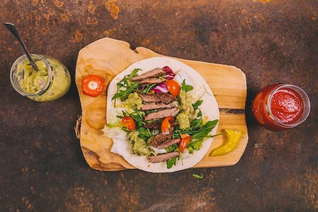 Tacos mexicanos com carne bovina; legumes frescos e guacamole com molho de salsa no fundo enferrujado