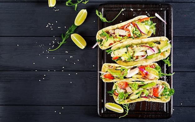 Tacos mexicanos com carne de frango, abacate, tomate, pepino e cebola vermelha.