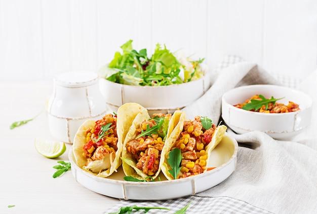 Tacos mexicanos com carne de frango, molho de milho e tomate.