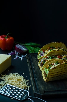 Tacos mexicanos com carne de porco, queijo, milho, cebola e ervas em uma placa de madeira