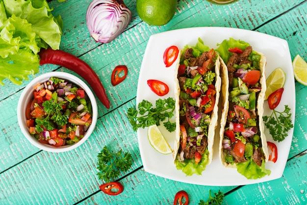 Tacos mexicanos com carne em molho de tomate e salsa