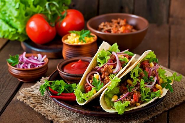 Tacos mexicanos com carne, legumes e cebola vermelha