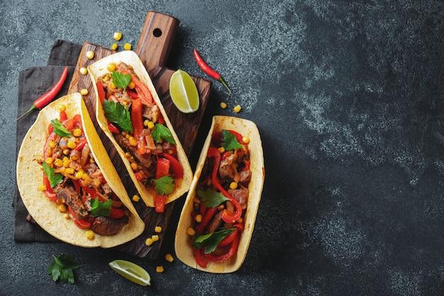Tacos mexicanos com carne, legumes e salsa.