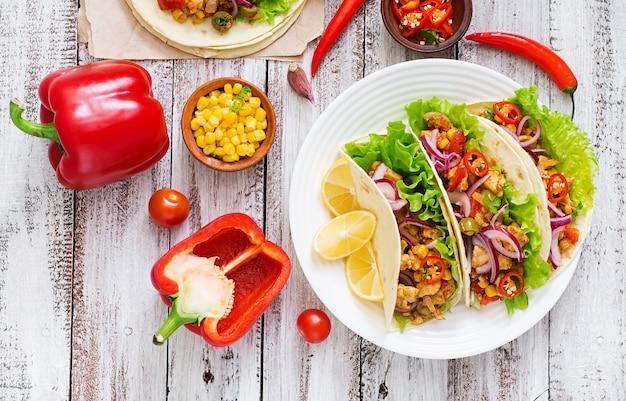 Tacos mexicanos com carne, milho e azeitonas em fundo de madeira. vista do topo