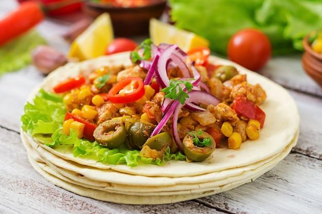 Tacos mexicanos com carne, milho e azeitonas em fundo de madeira.