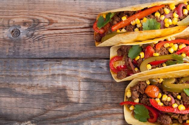 Tacos mexicanos com carne picada, legumes e salsa.