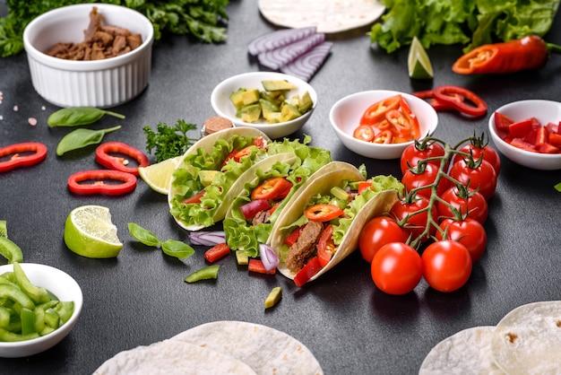 Tacos mexicanos com carne, tomate, abacate, cebola e molho de salsa