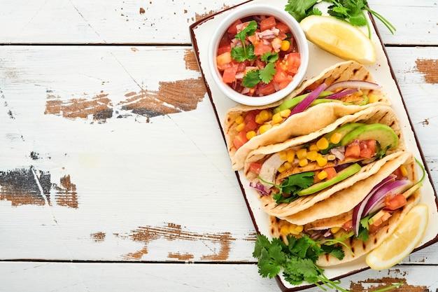 Tacos mexicanos com frango grelhado, abacate, grãos de milho, tomate, cebola, coentro e molho em mesa de pedra branca. comida de rua tradicional mexicana e latino-americana. vista do topo.