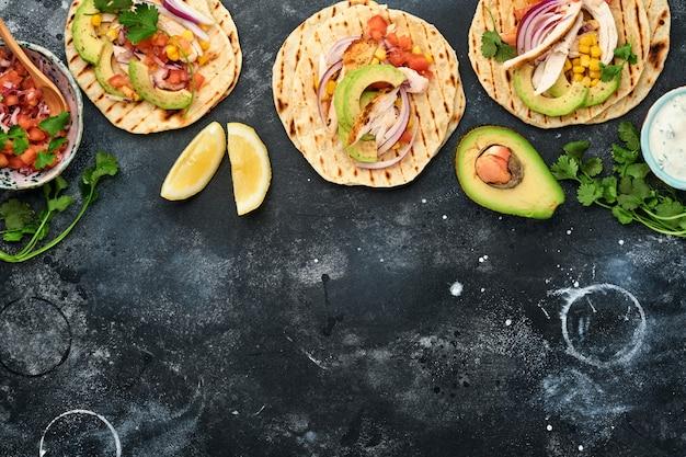 Tacos mexicanos com frango grelhado, abacate, grãos de milho, tomate, cebola, coentro e molho na mesa de pedra preta. comida de rua tradicional mexicana e latino-americana. vista do topo.