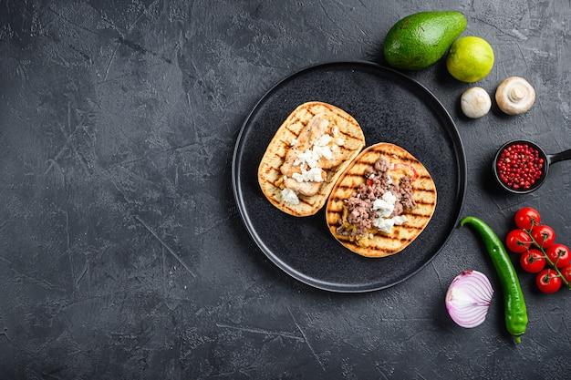 Tacos mexicanos com legumes e carne assada e frango na chapa redonda preta sobre fundo preto texturizado, vista superior com espaço para texto.