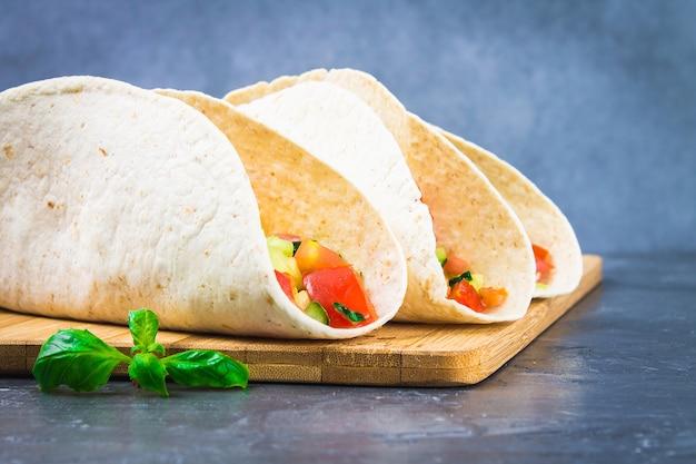 Tacos mexicanos tradicionais com carne e legumes em fundo de madeira
