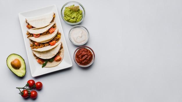 Tacos no prato perto de legumes e molhos