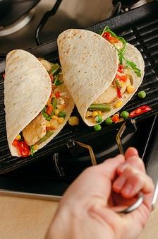 Tacos picantes mexicanos caseiros com frango e legumes na panela de grelhar.