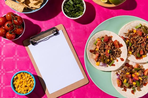 Tacos planos e arranjo de prancheta