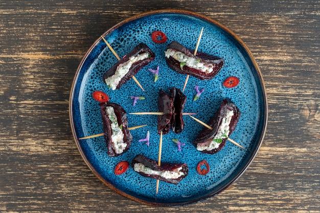 Tacos ucranianos feitos com rodelas de beterraba assadas recheadas com queijo de cabra, ervas, nozes e alho, close-up