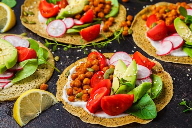 Tacos vegan com grão cozido, abacate, molho e legumes.