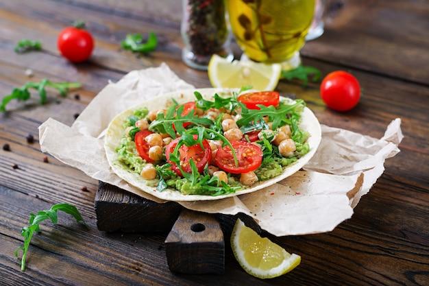 Tacos vegan com guacamole, grão de bico, tomate e rúcula. comida saudável. pequeno-almoço útil