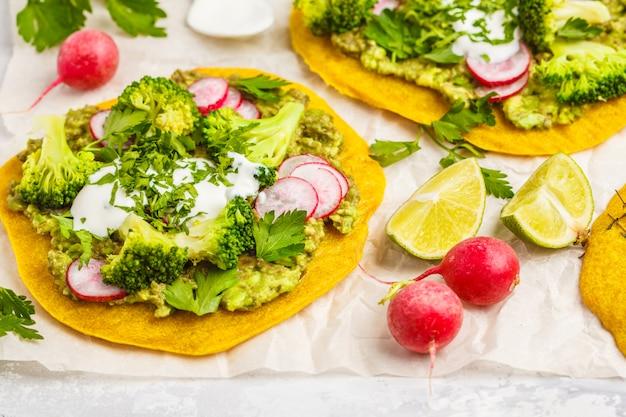 Tacos vegan (pizza, pita) com rabanete, brócolis e guacamole, vista de cima. conceito de comida vegana saudável.